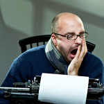 Serious bald man in scarf and glasses yawning